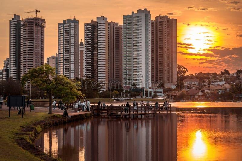 与大厦的金黄小时在一个湖的水反射了在公园 公园甲板的某些人享受看法的 免版税库存图片