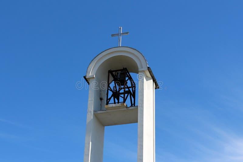 与大开放金属响铃机制的现代白色教堂钟塔和在上面的发光的钢十字架与清楚的天空蔚蓝在背景中 免版税库存照片