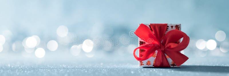 与大弓的美好的红色圣诞礼物在发光的蓝色背景和defocused圣诞灯在背景中 免版税库存图片