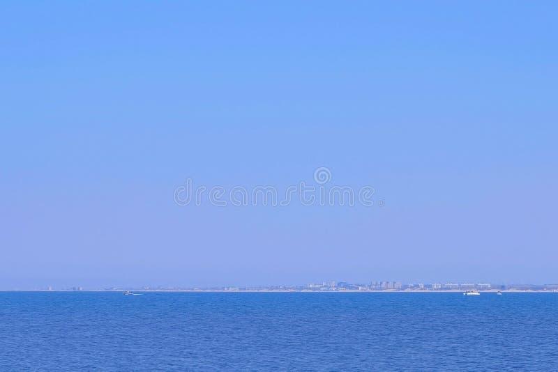 与大海、游艇、城市距离的和清楚的天空的海景背景 免版税库存照片