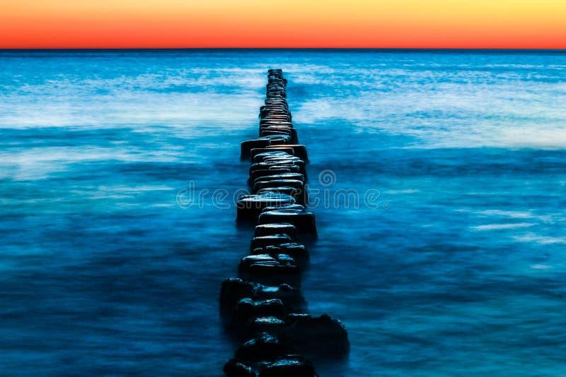 与大海和红色日落的木groynes 长期风险 库存照片
