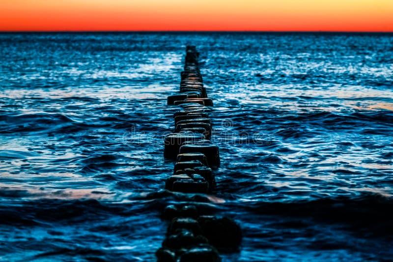 与大海和红色日落的木groynes 免版税库存图片