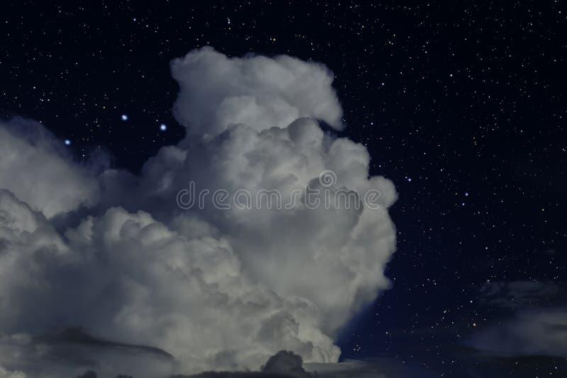 与大白色云彩的夜满天星斗的天空 图库摄影