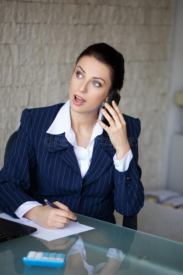 与大眼睛的Businsswoman由电话得到好消息 库存照片