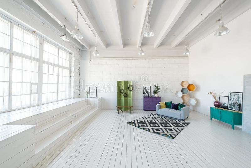 与大窗口,高顶,白色木地板,现代沙发的明亮的照片演播室或客厅内部其他 免版税库存照片