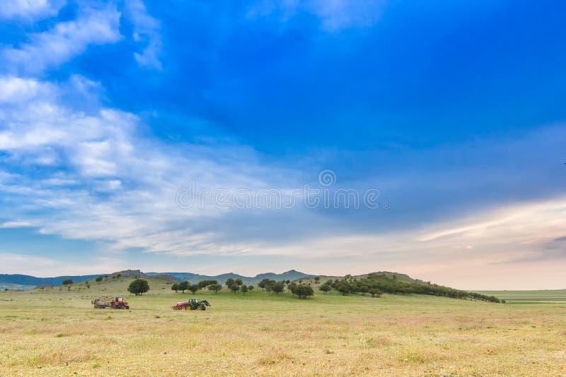 与大蓝天的美好的农村风景在小山和收割者和犁车 库存照片