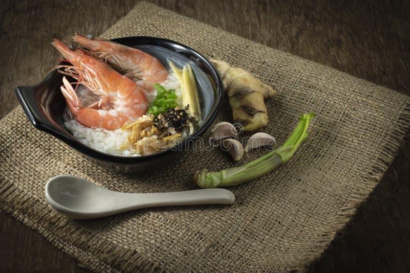 与大虾和姜混合的米稀饭,薤切片和被油炸的大蒜和黑胡椒在黑碗 香料投入了右边 免版税库存照片