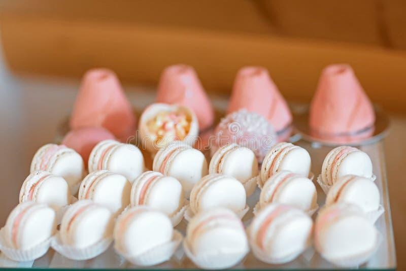 与大蛋糕,杯形蛋糕,蛋糕的典雅的甜桌在晚餐或事件党流行 有可口蛋糕和蛋白杏仁饼干的盘子 承办酒席 图库摄影