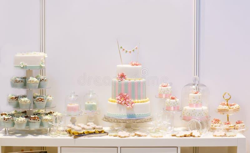 与大蛋糕,杯形蛋糕,蛋糕的典雅的甜桌在晚餐流行 库存照片