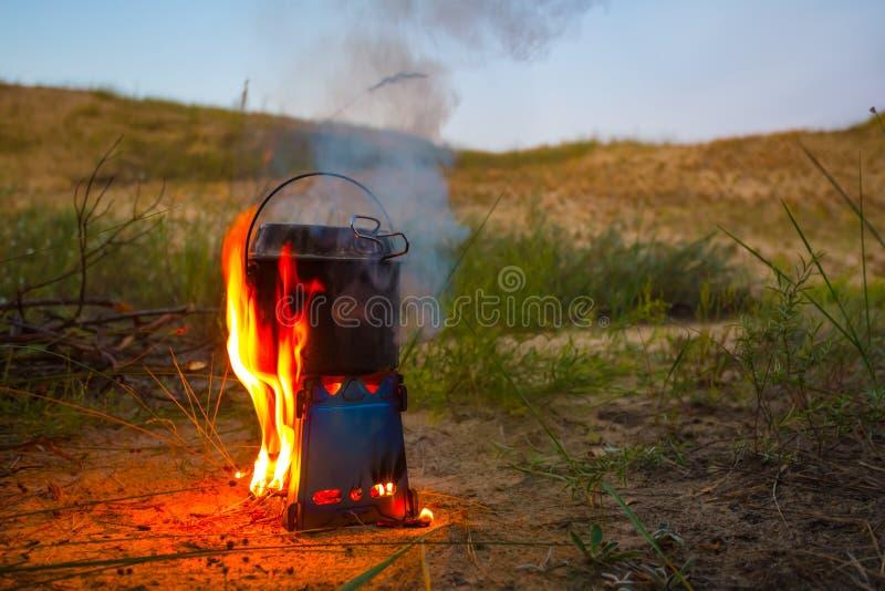 与大锅的特写镜头灼烧的木头手提油炉 免版税库存照片