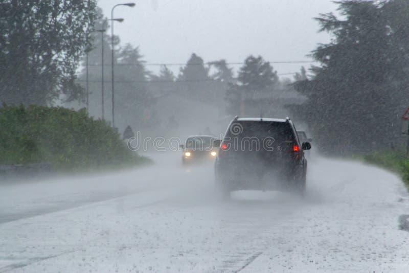 与大雨的强的风暴在有汽车的恶劣的可见性的路 库存图片