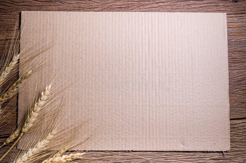 与大麦五谷的纸板纸在木桌上 库存照片