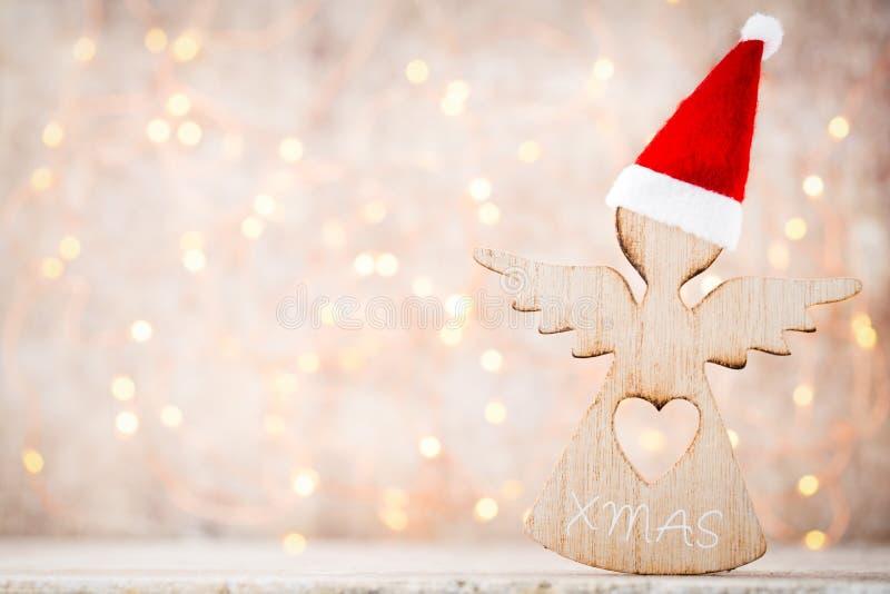 与天使圣诞老人帽子的圣诞节装饰 葡萄酒背景 免版税库存照片