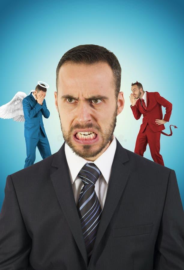 与天使的他的肩膀的商人和恶魔 免版税库存图片