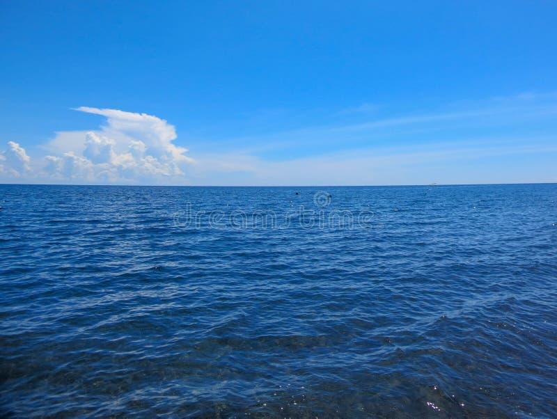 与天空蔚蓝和微小的云彩的美好的海风景在好日子在印度尼西亚 与海天线和几乎清楚深的海景 库存图片