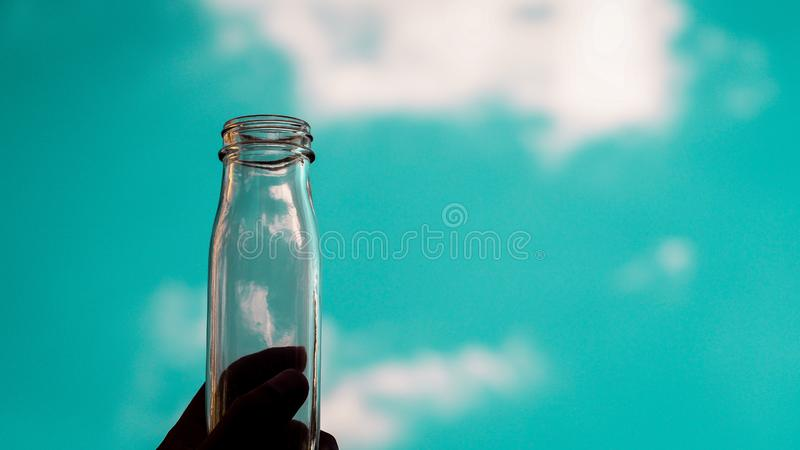 与天空蔚蓝的手举行透明空的瓶积土 库存图片