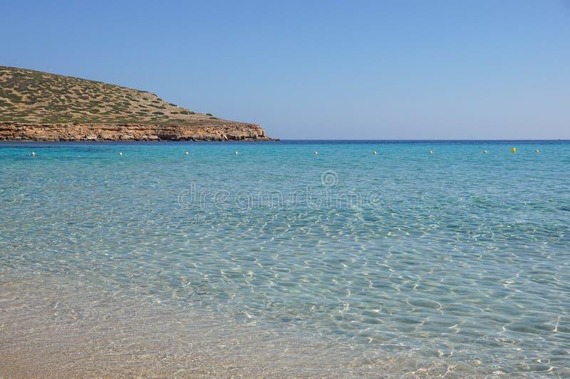 与天蓝色的蓝色海水,伊维萨岛海岛,西班牙的美丽的含沙卡拉市孔德海滩 免版税图库摄影