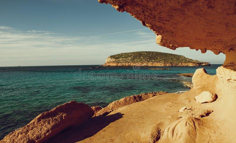 与天蓝色的蓝色海水,伊维萨岛海岛,西班牙-图象的美丽的含沙卡拉市孔德海滩 免版税库存图片