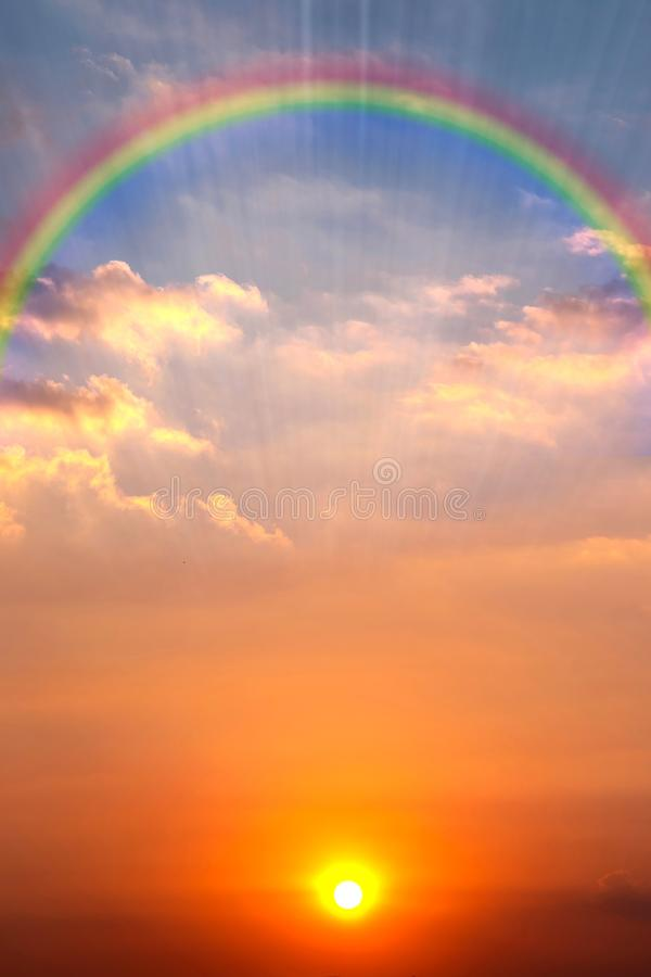 与太阳、彩虹和太阳光芒的美丽的日落天空 免版税库存照片