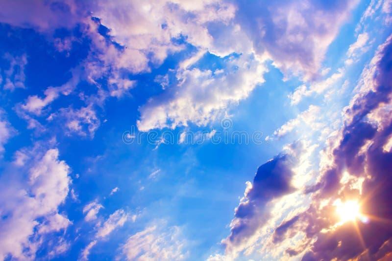 与太阳光芒和蓝天的美好的五颜六色的日落与云彩 免版税图库摄影