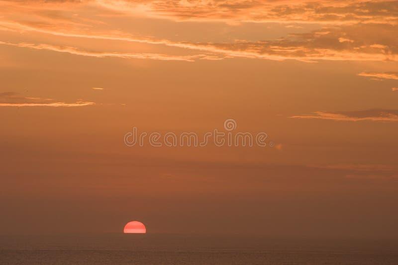 与太阳和云彩的天空在日落期间 库存照片