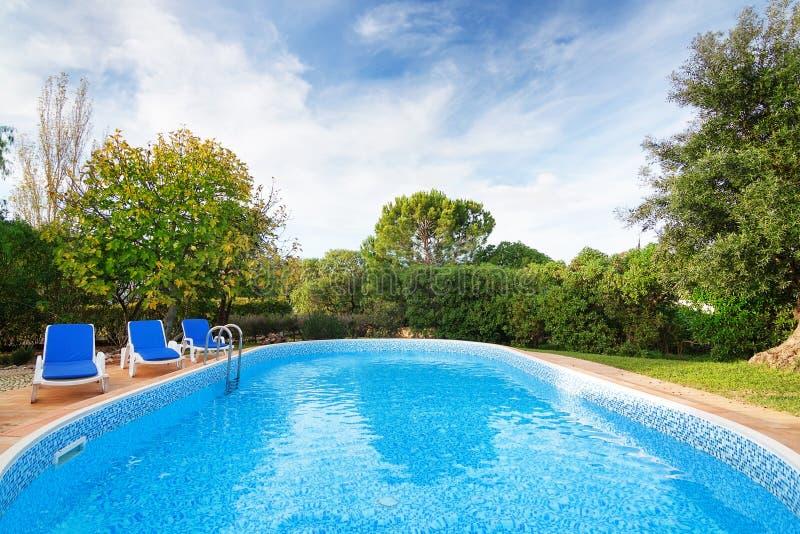 与太阳懒人的豪华夏天游泳池。 库存图片