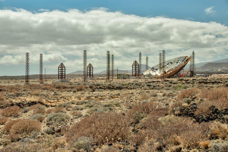 与太阳电池板的巨大的抛物面盘 生产的被放弃的建筑enegy 使用为甲醇和煤炭的生产 El 免版税图库摄影