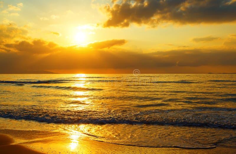与太阳的五颜六色的黎明通过云彩发出光线在海和含沙岸 构成设计要素本质天堂 图库摄影