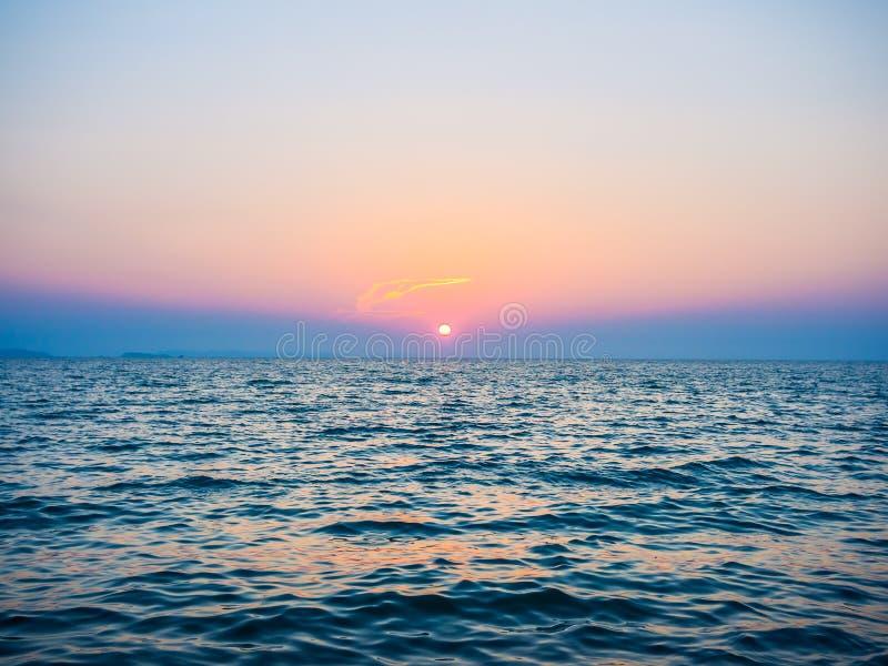 与太阳的美丽的日落天空和在云彩的意想不到的金黄线在深蓝色海 免版税库存图片