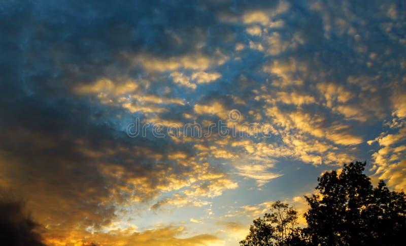 与太阳的美好的天堂般的风景在云彩天空,明亮的蓝色,橙色和黄色颜色日落 免版税库存图片
