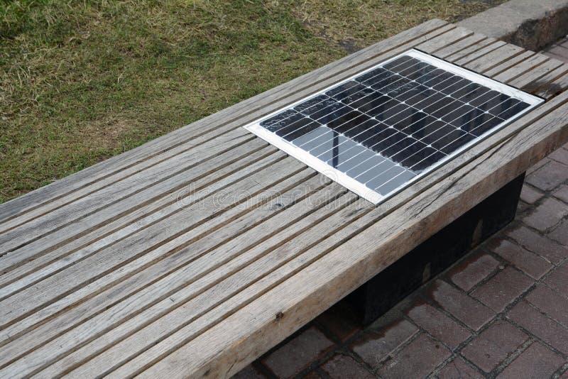 与太阳能电池的长凳 太阳充电的长凳,供给动力的太阳连接设备在室外 免版税库存图片