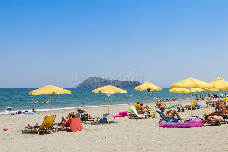 与太阳遮阳伞和sunloungers的普拉坦亚斯海滩 库存图片