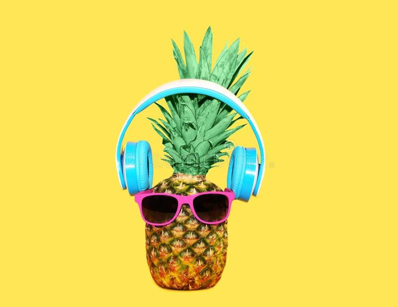 与太阳镜和耳机的时尚菠萝听在黄色背景,凤梨概念的音乐 库存图片