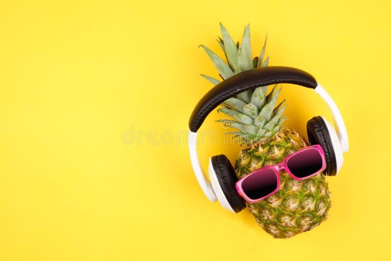 与太阳镜和耳机的行家菠萝在黄色背景 库存照片