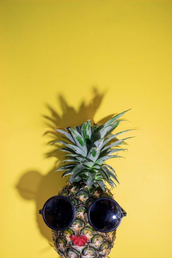 与太阳镜的成熟红色嘴唇菠萝在黄色背景,拷贝空间,最小的夏天概念 库存照片