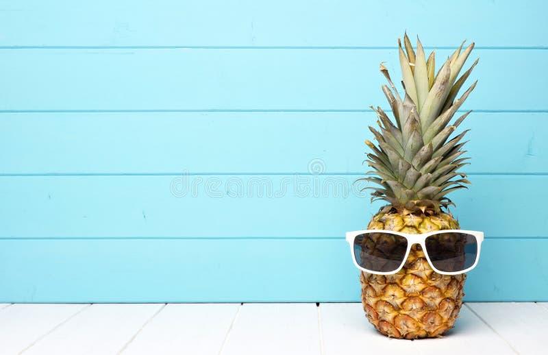 与太阳镜的行家菠萝反对蓝色木头 免版税图库摄影