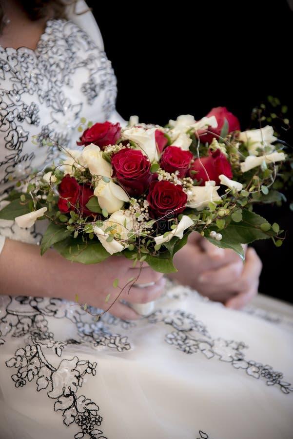 与夫妇的婚姻的玫瑰色花束 免版税库存照片