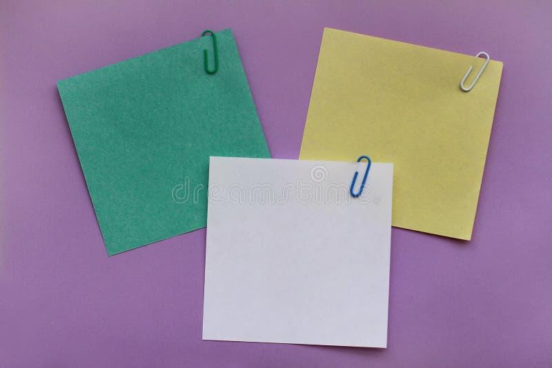 与夹子的空白的便条纸标签在紫罗兰色背景 图库摄影