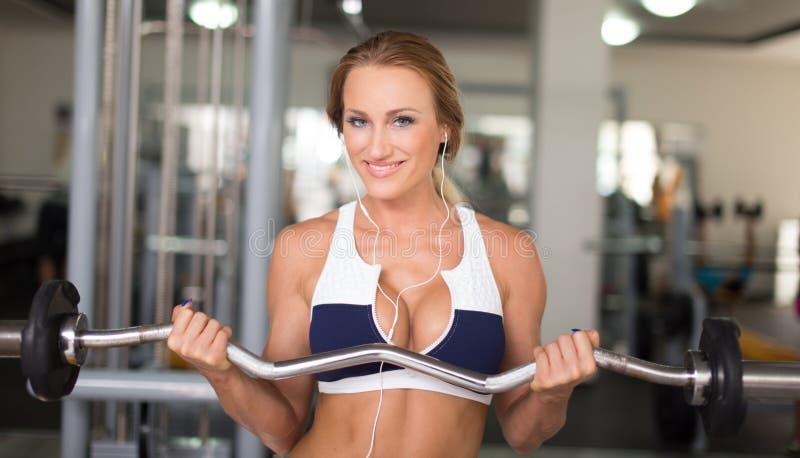 与奥林匹克酒吧的年轻白肤金发的妇女锻炼在健身房 图库摄影