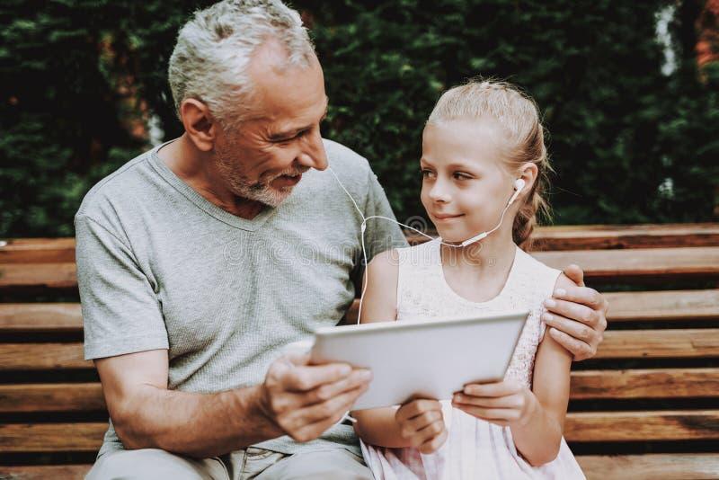 与女孩的年长芦苇书 男人和妇女 库存图片