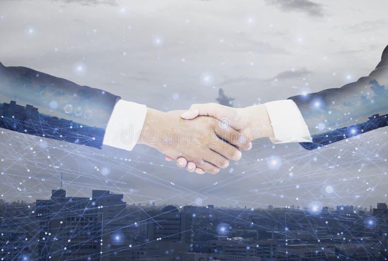 与女实业家成交的双重曝光商人握手和同意谈判完全的使命,背景都市风景与 免版税库存照片