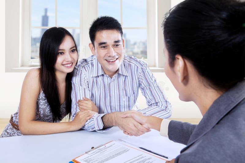 与女实业家的亚洲夫妇手震动 免版税库存照片