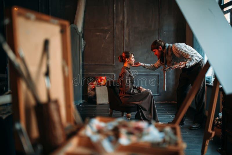 与女性伪装者的男性艺术家工作在艺术演播室 库存图片