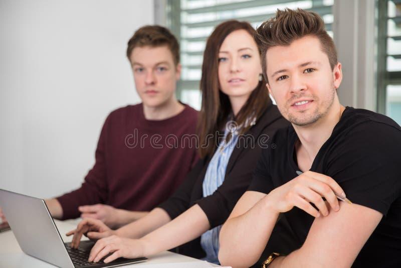 与女性同事的确信的商人在办公室 免版税库存照片