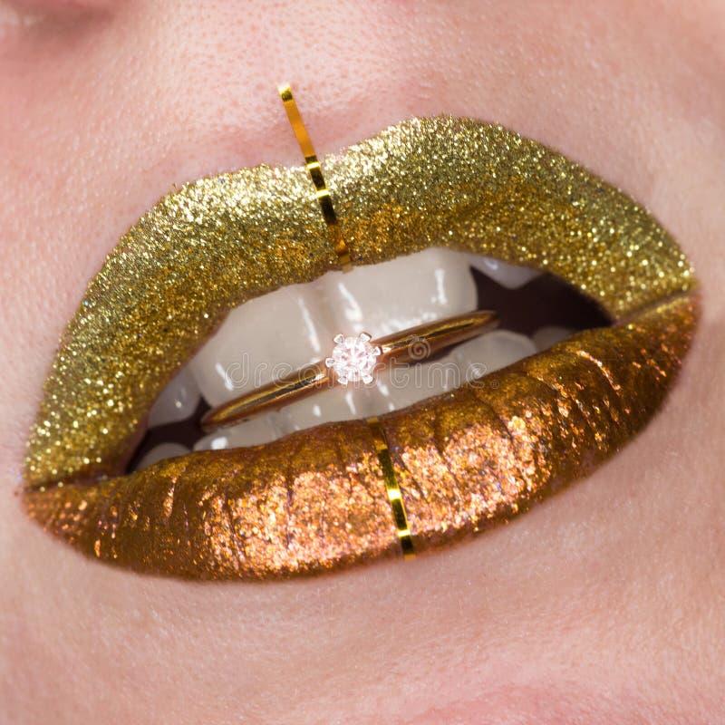 与女性肥满嘴唇的美丽的特写镜头有金子颜色构成的 闪烁化妆用品 与精采的金黄圆环在嘴 免版税库存照片