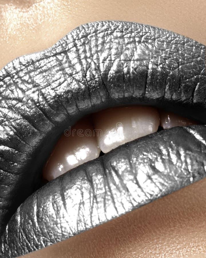 与女性肥满嘴唇的美丽的特写镜头有银色颜色构成的 圣诞节庆祝构成,在嘴唇的闪烁闪闪发光 免版税图库摄影