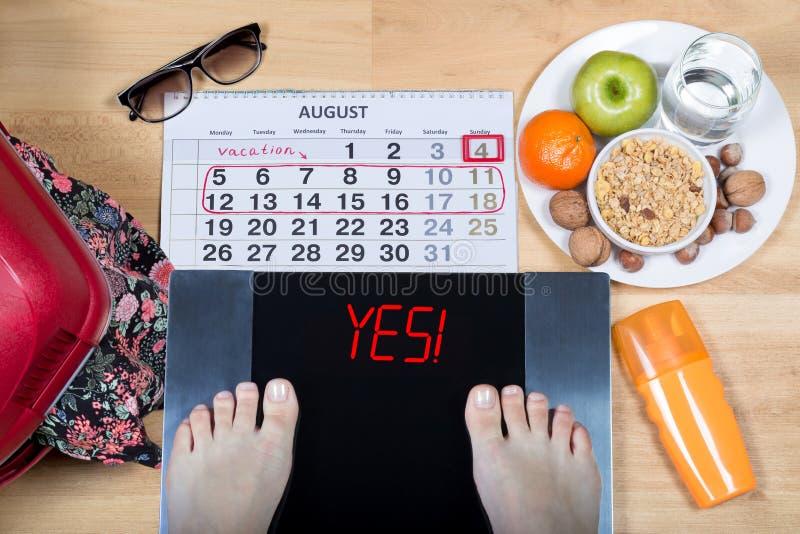 与女性脚的数字式标度是签署`! 日历、夏天辅助部件和板材围拢的`用健康食物 免版税库存照片