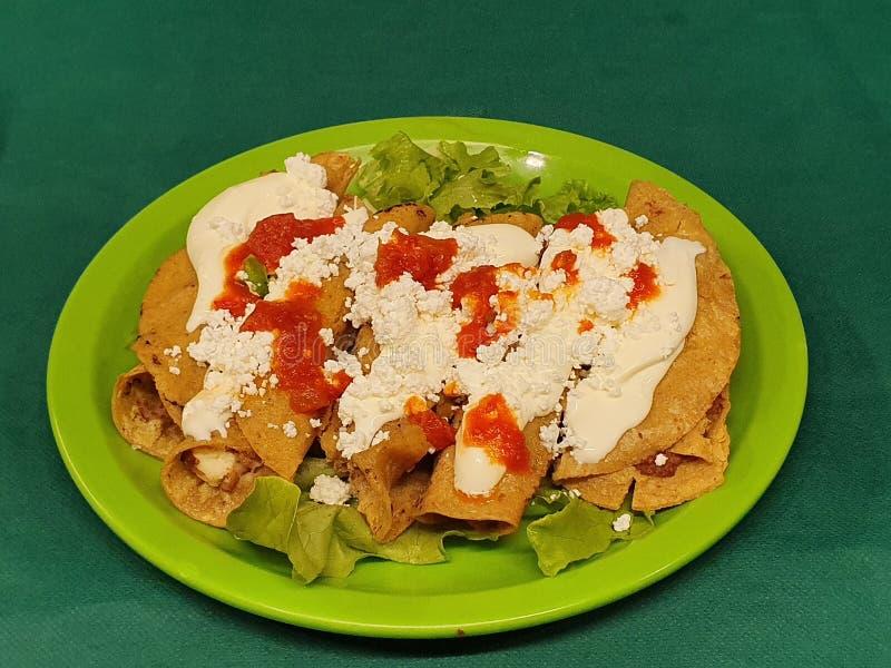 与奶油、乳酪和辣红色调味汁,传统墨西哥美食的油煎的炸玉米饼 免版税图库摄影