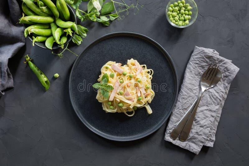 与奶油、豌豆和烟肉的面团tagliatelle在黑背景 E 库存图片