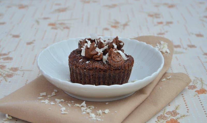 与奶油和巧克力削片的杯形蛋糕 库存照片